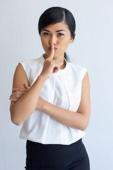 Impiegato di concetto asiatico serio che mantiene segreto