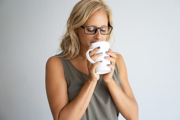 Impiegato di concetto femminile ispirato che gode dell'intervallo per il caffè.