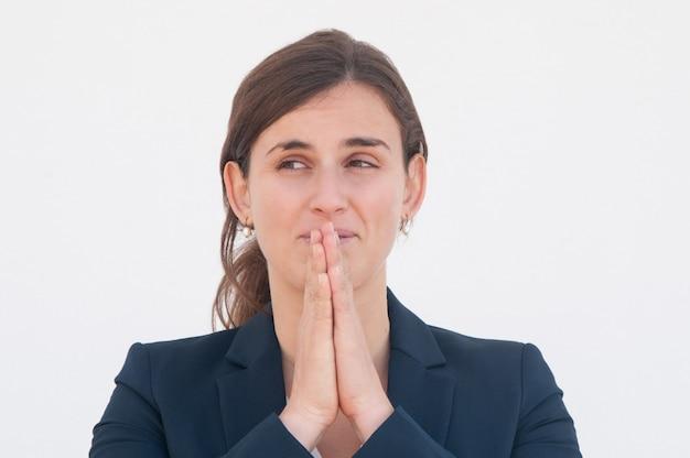 Impiegato di concetto positivo che prega per fortuna