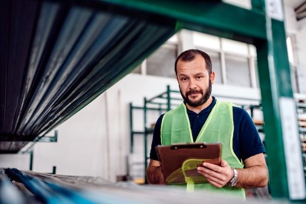 Impiegato di controllo che controlla l'inventario del magazzino nella fabbrica industriale