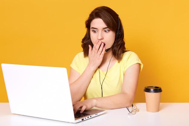 Impiegato emotivo impressionato che applica le informazioni, lavorando con i clienti attraverso il computer portatile, sembra sorpreso, sventola la bocca con una mano, indossa una maglietta gialla casual. concetto di ufficio.