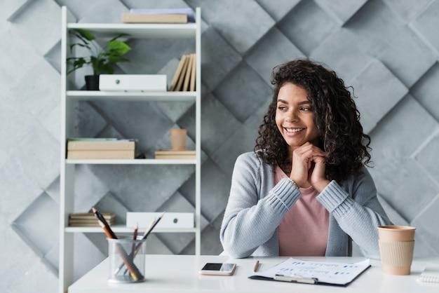 Impiegato etnico che si siede nel luogo di lavoro in ufficio
