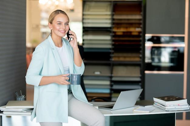 Impiegato giovane impiegato che mangia tè o caffè mentre parla con qualcuno tramite smartphone
