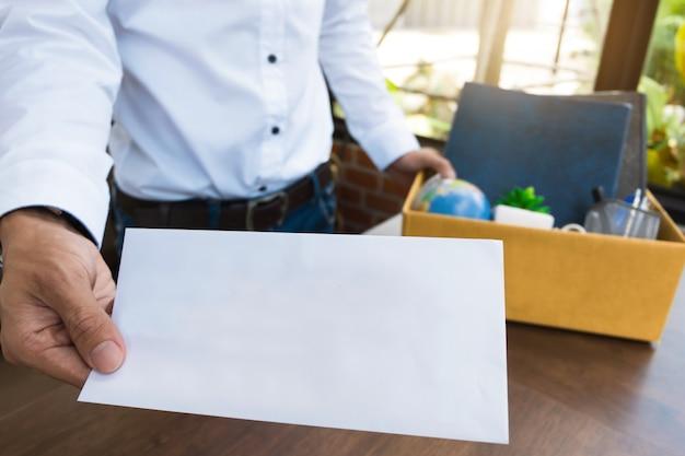 Impiegato in possesso di lettera di dimissioni e imballaggio di una casella per lasciare l'ufficio