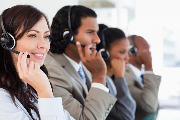 Impiegato sorridente della call center che lavora mentre accompagnato dalla sua squadra