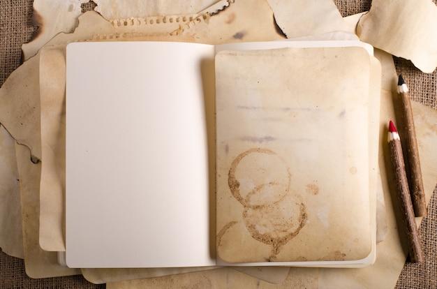 Impila vecchie carte, quaderno e matite di legno su tela, tela di sacco.