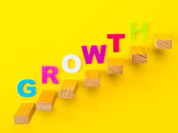 Impilamento di blocchi di legno come gradini con colorate parole di growth