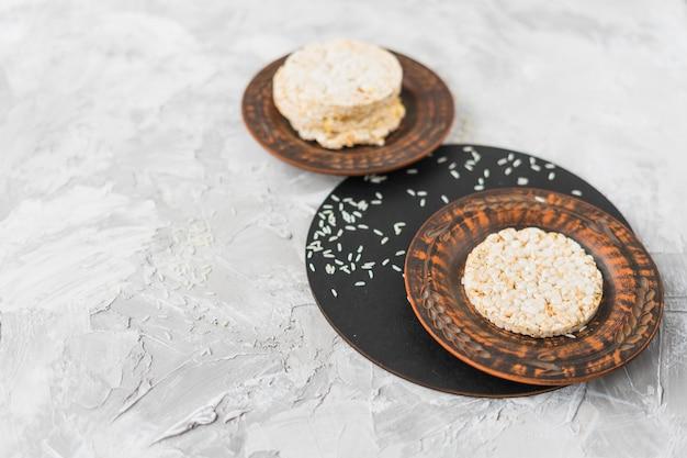 Impilati del dolce di riso soffiato con i grani su fondo strutturato bianco
