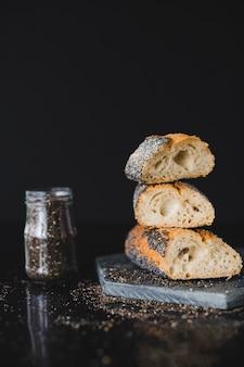 Impilati delle fette del pane con i semi di chia su roccia contro fondo nero