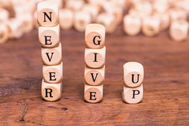 Impilati di blocchi di legno con la parola non mollare mai sulla scrivania in legno