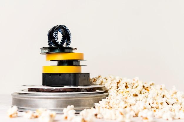 Impilati di bobine di film con la striscia di pellicola sulla parte superiore vicino al popcorn su sfondo bianco