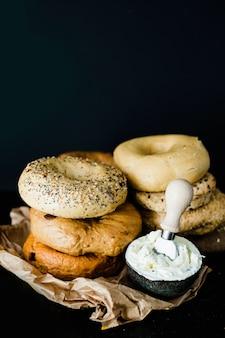 Impilati di diversi tipi di bagel con formaggio nella ciotola contro sfondo nero