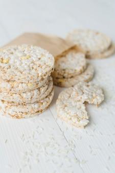 Impilati di riso soffiato con grani sul tavolo di legno bianco