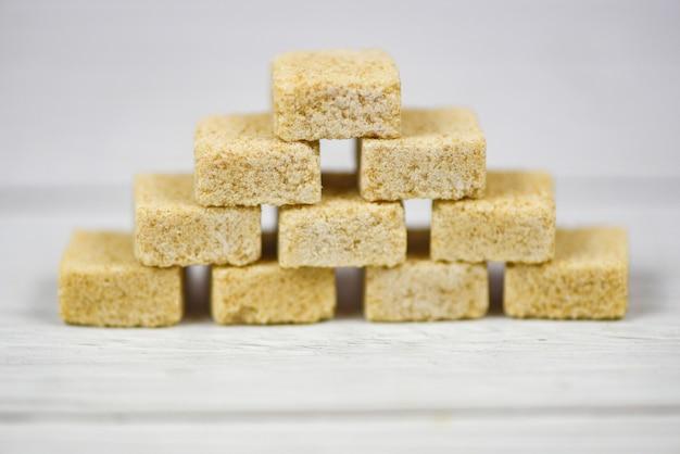 Impilato dei cubi dello zucchero bruno sul fondo della tavola - zucchero alto vicino