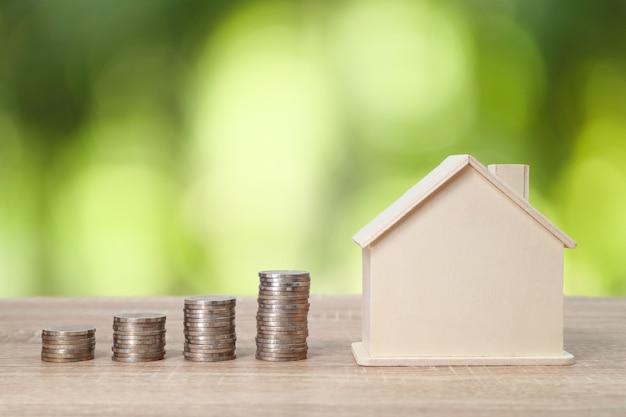 Impili le monete con la casa sulla tavola di legno