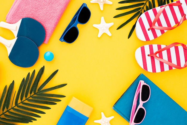 Impostare per una vacanza al mare in spiaggia: asciugamano, occhiali da sole, infradito, foglie, stelle marine e crema solare