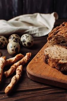 Impostare un pane di grano saraceno senza lievito scuro in un taglio si trova su una tavola di legno