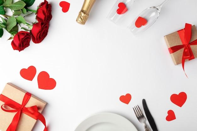Impostazione del luogo, rose e regali sul tavolo bianco