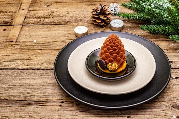 Impostazione del posto per la cena di natale e capodanno. spuntino dolce, ramo di abete, candele, coni, piatti in ceramica, forchetta e coltello.
