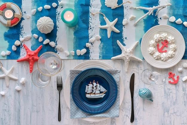 Impostazione del tavolo da pranzo del columbus day con decorazioni nautiche del mare sul corridore a strisce blu