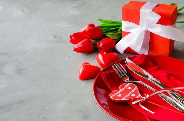 Impostazione del tavolo festivo per san valentino con confezione regalo e tulipani.