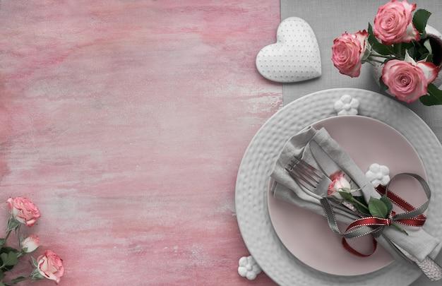 Impostazione del tavolo per san valentino, compleanno o anniversario, vista dall'alto su superficie rosa chiaro, copia-spazio