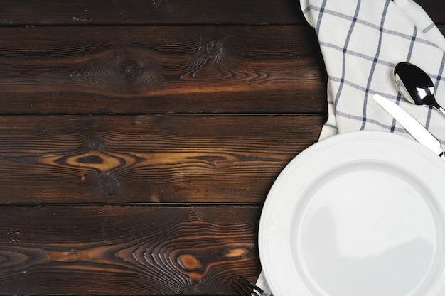 Impostazione della tabella con piastre su fondo di legno scuro