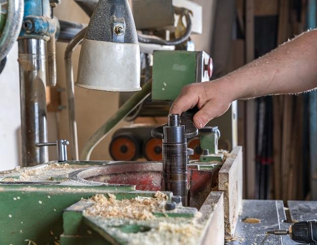 Impostazione della taglierina con l'aiuto di una maniglia nella falegnameria