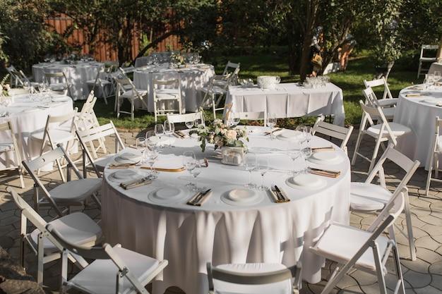 Impostazione della tavola di nozze. tavolo per banchetti all'aperto per gli ospiti con vista sul verde