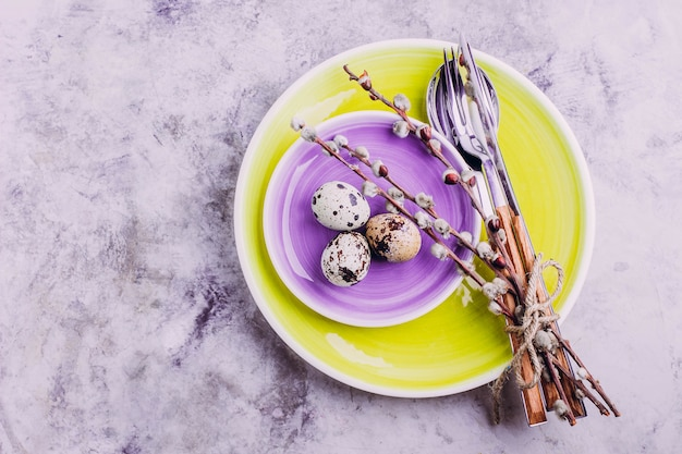 Impostazione della tavola di pasqua. piatto giallo e viola, posate, uova di quaglia e salice