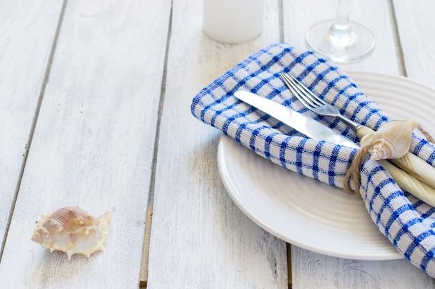 Impostazione della tavola in stile marino sul piatto con conchiglie