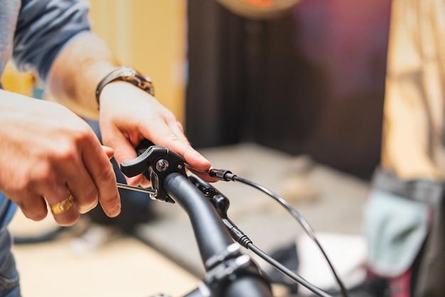 Impostazione delle pause di una bicicletta, vista ravvicinata. mani umane che riparano una bicicletta in un negozio di biciclette locale