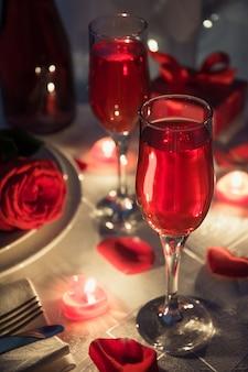 Impostazione di bicchieri con candele, champagne, bottiglia e confezione regalo sul tavolo romantico. cena di san valentino