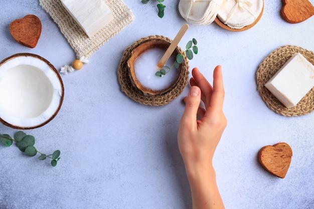 Impostazione di prodotti cosmetici naturali con saponi e erbe fresche vista dall'alto mani di donna