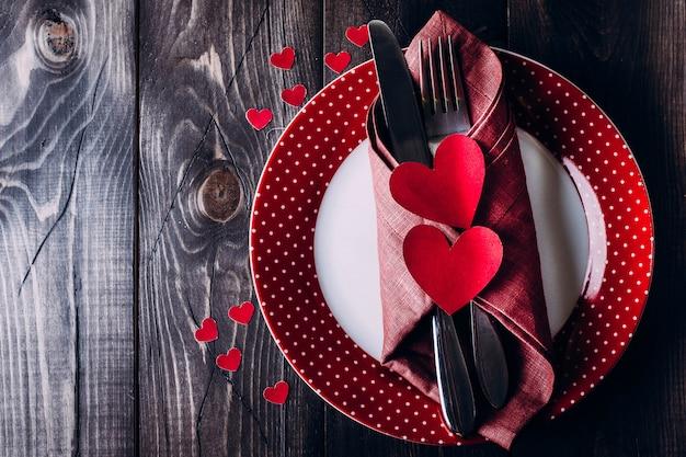Impostazione tabella giorno di san valentino. piatto, coltello e forcella rosa sulla tavola di legno del fondo.