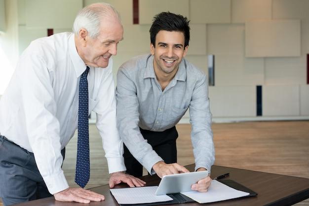 Imprenditore allegro che mostra applicazione al collega
