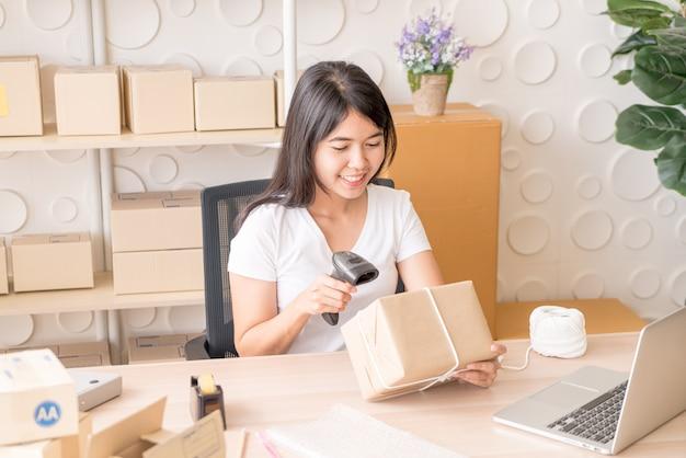 Imprenditore asiatico della donna che lavora a casa con il contenitore di imballaggio sul posto di lavoro