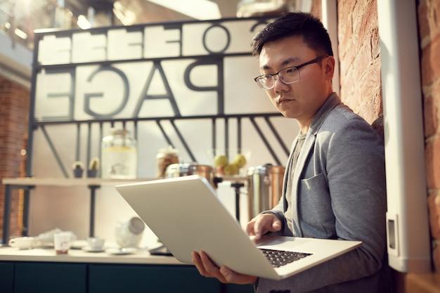 Imprenditore asiatico holding laptop