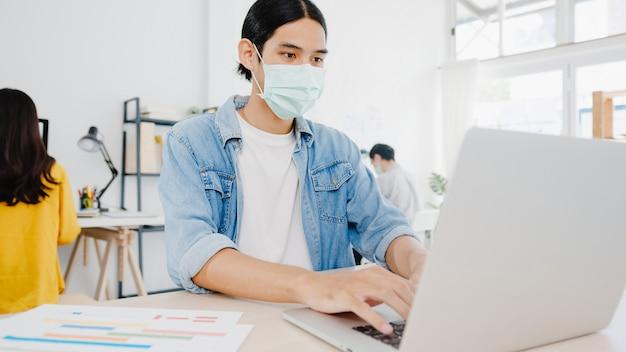 Imprenditore asiatico uomo d'affari che indossa una maschera medica per l'allontanamento sociale in una nuova situazione normale per la prevenzione dei virus mentre si utilizza il laptop al lavoro in ufficio. stile di vita dopo il virus corona.