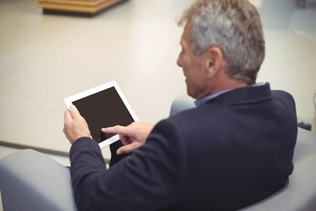 Imprenditore attento seduto sul divano e utilizzando la tavoletta digitale