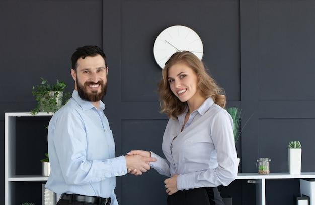 Imprenditore barbuto e imprenditrice agitando le mani in ufficio