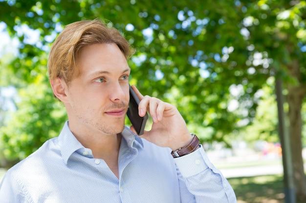 Imprenditore calmo positivo che rivolge al telefono cellulare