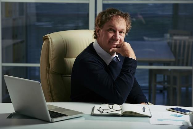 Imprenditore caucasico seduto al suo tavolo da ufficio con un volto fiducioso