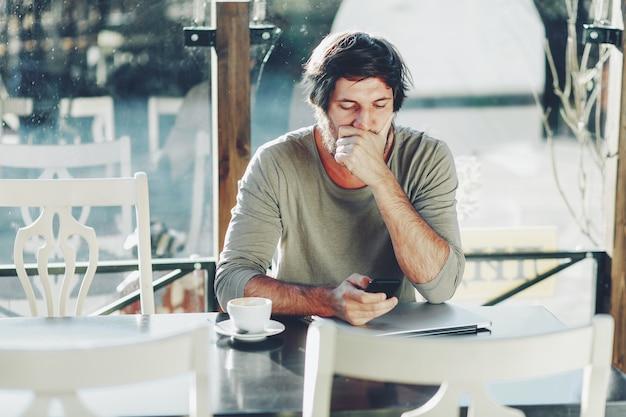 Imprenditore che parla al telefono con sguardo sorpreso, scioccato da alcune inattese notizie negative relative alla sua attività, toccandosi il viso, lavorando al computer portatile in un bar