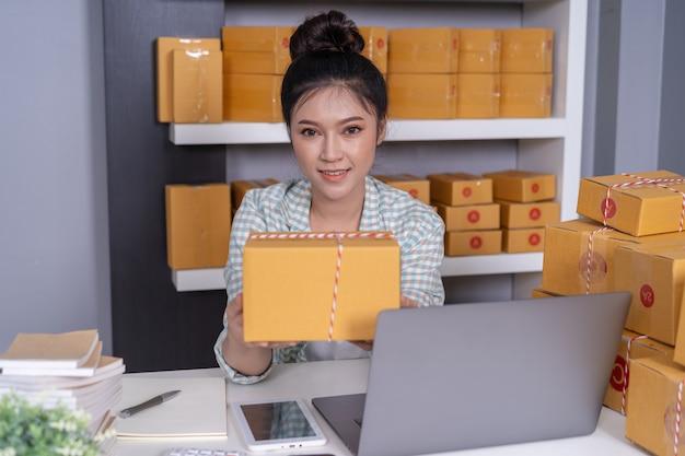 Imprenditore della donna con le cassette del pacchetto nel suo proprio lavoro che compera affare online a casa