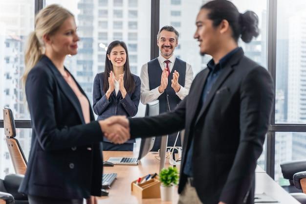 Imprenditore e imprenditrice si stringono la mano nel corso di una riunione
