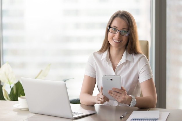 Imprenditore femminile che utilizza compressa digitale nell'ufficio