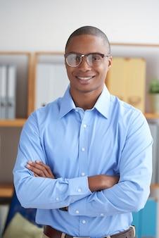 Imprenditore fiducioso guardando la fotocamera con le braccia conserte sorridendo