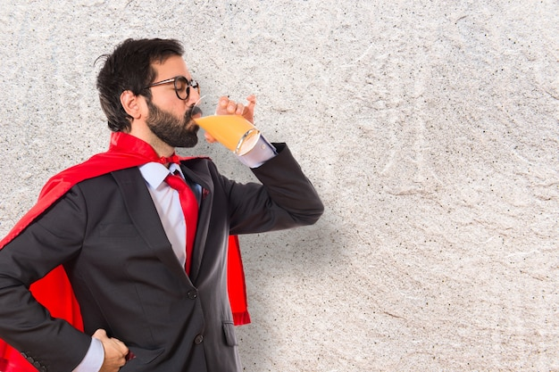 Imprenditore hipster vestito come supereroe bere succo d'arancia