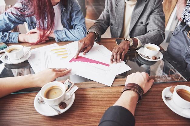 Imprenditore multietnico, concetto di piccola impresa. donna che mostra ai colleghi qualcosa sul computer portatile mentre si riuniscono intorno ad un tavolo da conferenza